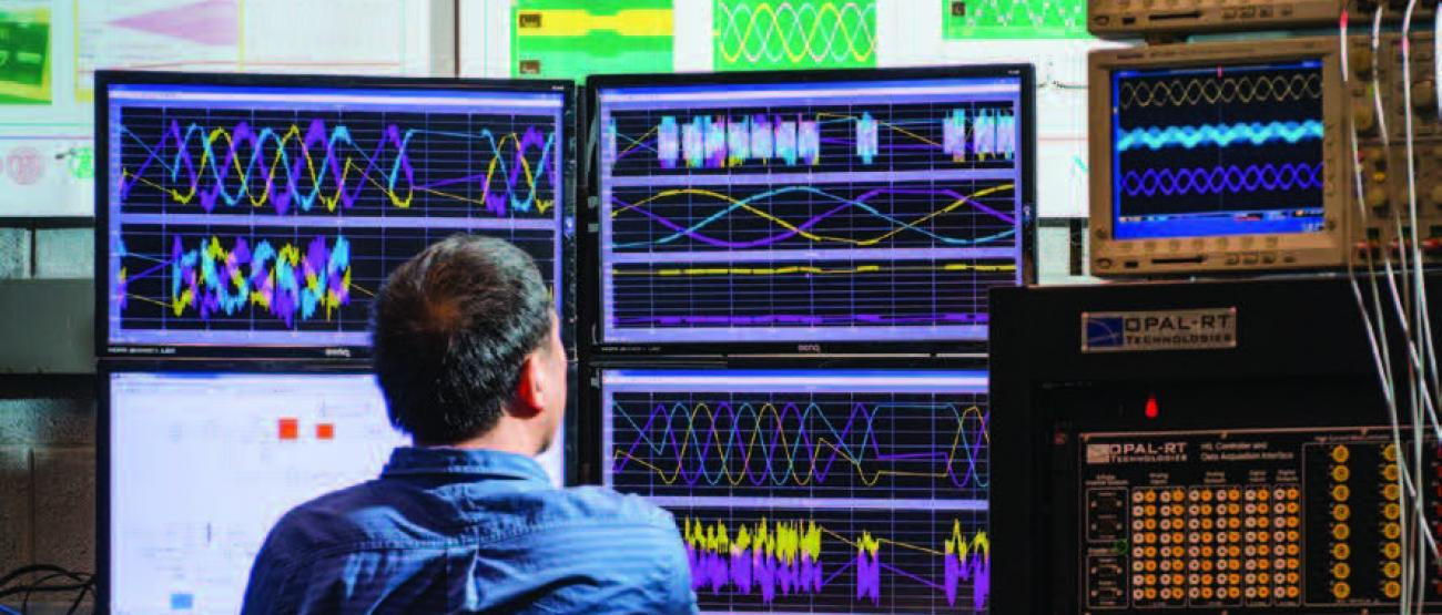 Researcher reviewing multiple screens of data