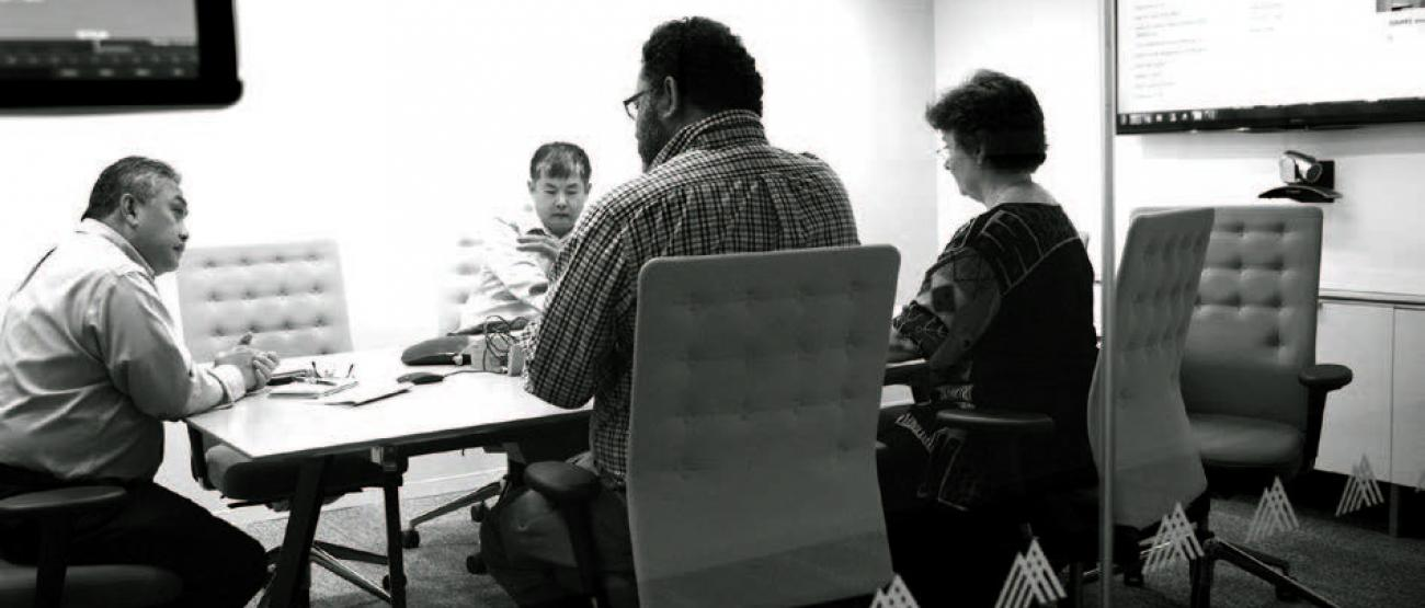 A group of people sitting at a conference table.