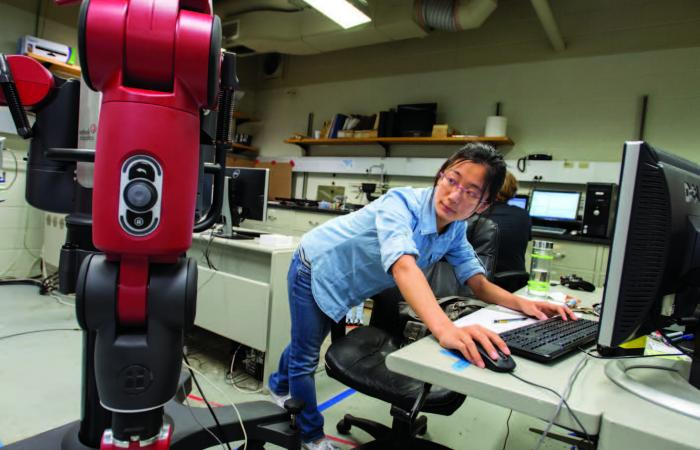 Woman working with robotic equipment.