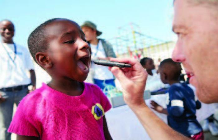 Shot of a volunteer doctor giving checkups to underprivileged kids