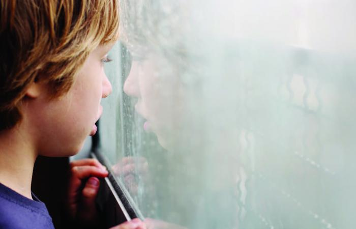 Photo of a young child looking out a window.